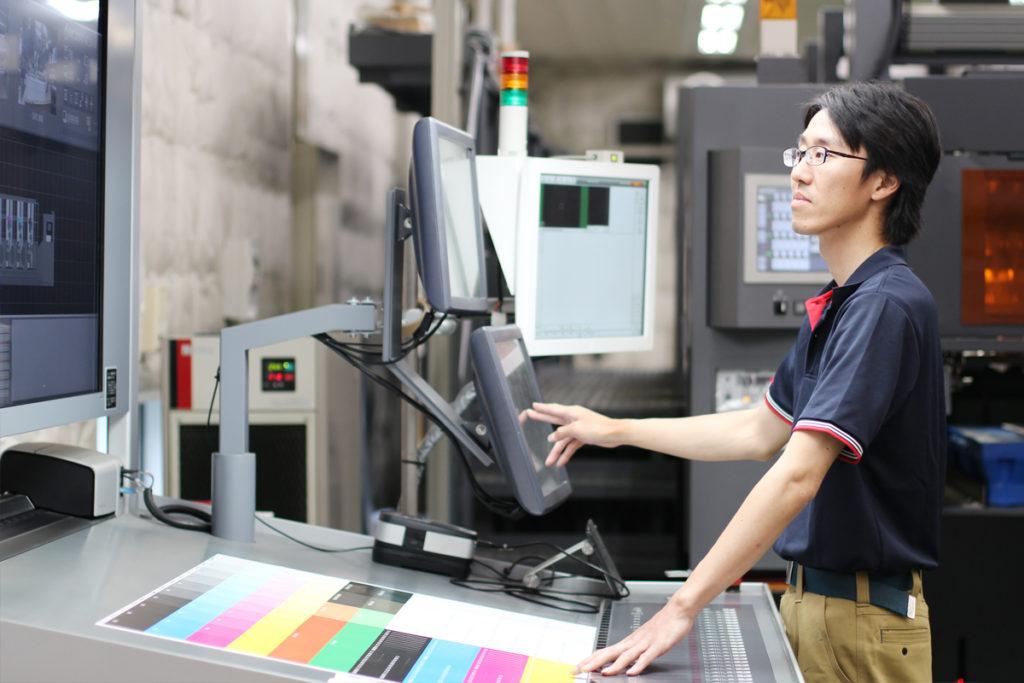 色をチェックしながら印刷機の設定を調整