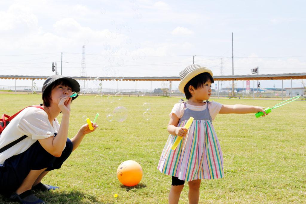 休日に公園で子どもと遊ぶ風景