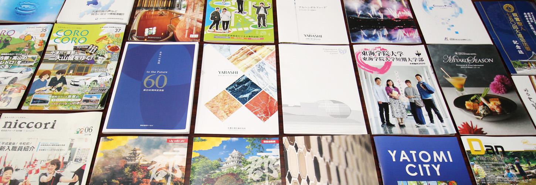 過去に作った商業印刷物を並べたイメージ写真
