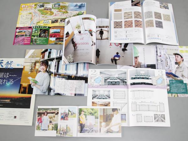 過去に作った商業印刷物の冊子を開いて中が分かるように並べたイメージ写真